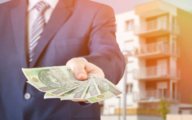 Polish businessman holds money. The loan on the house. Money loan polish pln cash banknote apartment flat concept